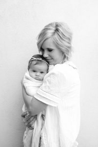 mom holding her newborn daughter - Learn Eat Sleep